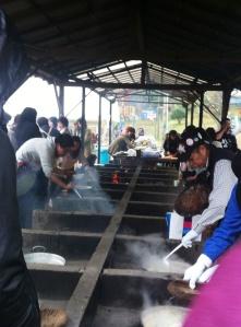 Dapur umum, memasak di atas tungku dengan kayu bakar.
